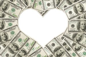 One hundred dollar bills in the shape of a heart isolated on white background The love of money